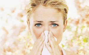 Young woman blowing nose on tissue, close up, portrait